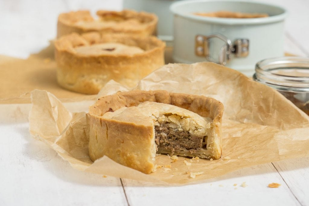 Scotch Pie Recipe - Scotch pie with slice cut out sitting on baking paper with other pies behind and pie tin