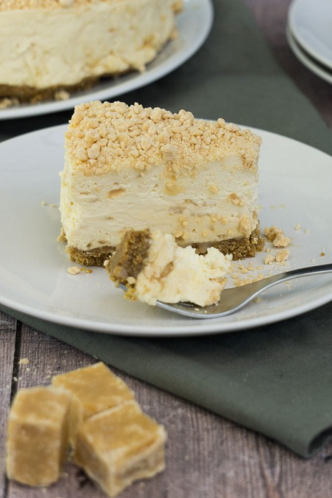 Slice of Scottish Tablet Cheesecake recipe on a plate with fork and bite taken out of it