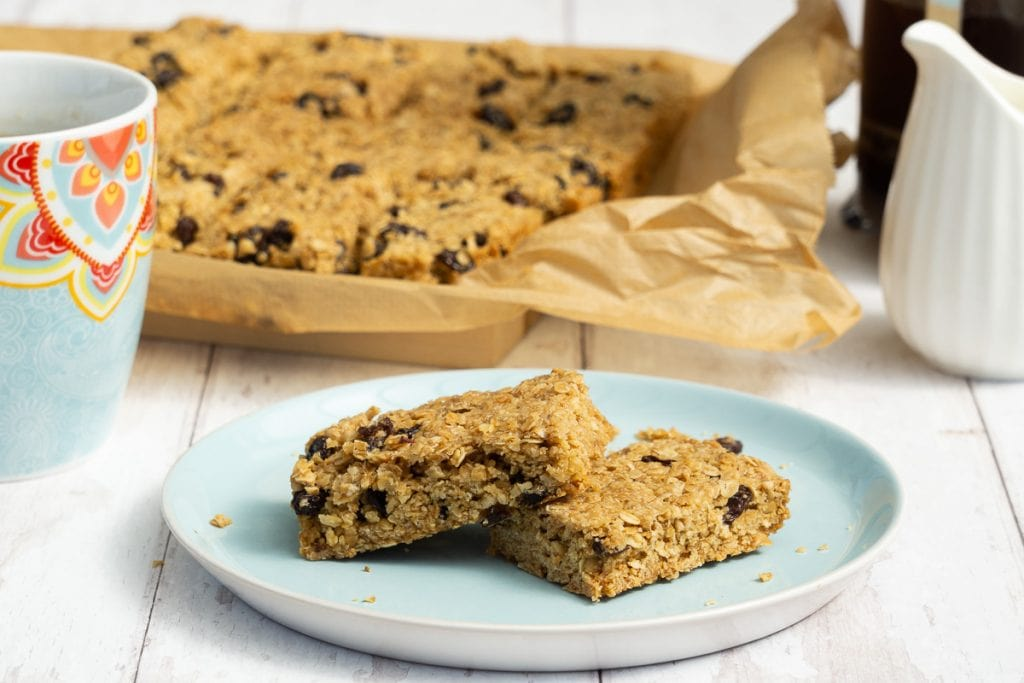 Sultana and Raisin Flapjacks on a plate with coffee cup and milk