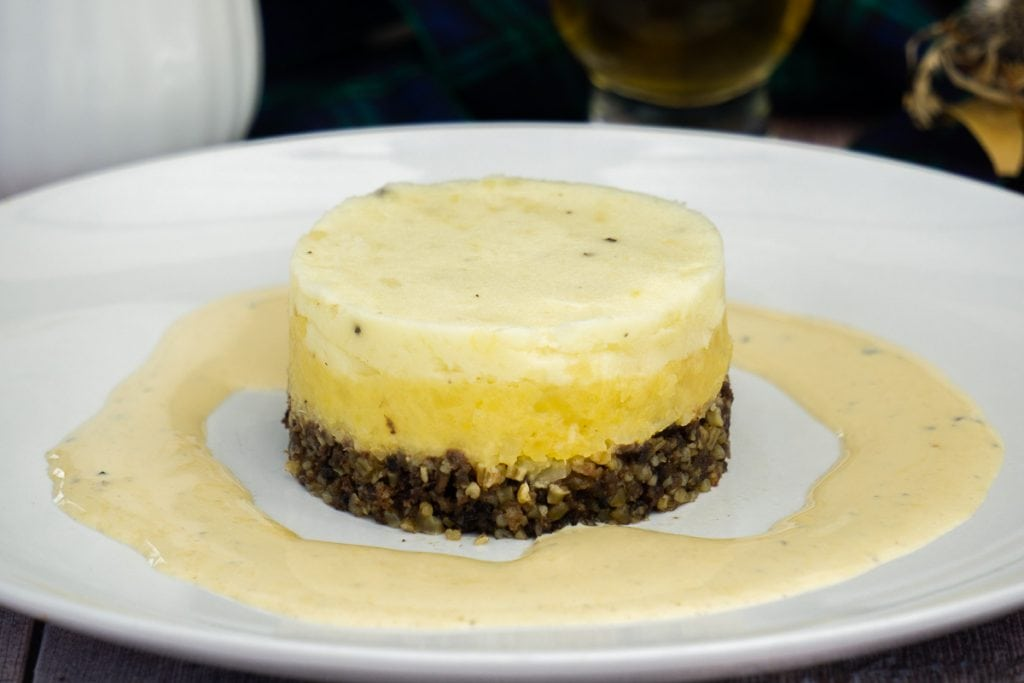 Haggis neeps and tatties and whisky sauce on a white plate
