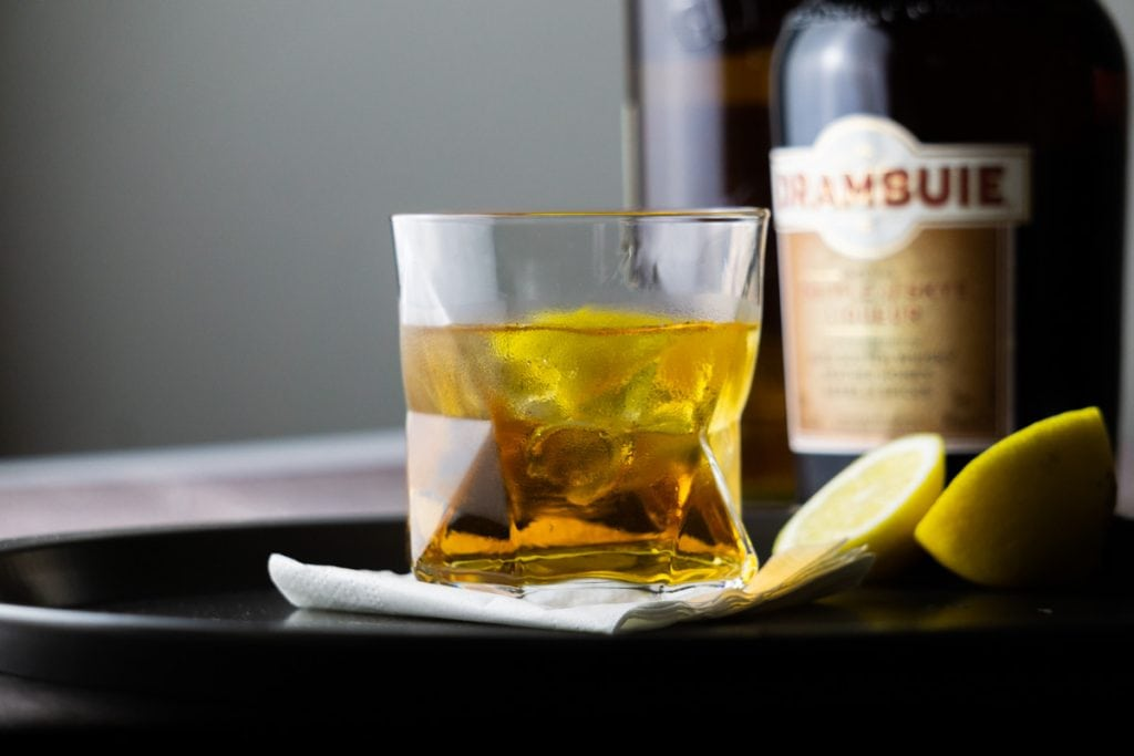A Rusty Nail cocktail and bottle of Drambuie