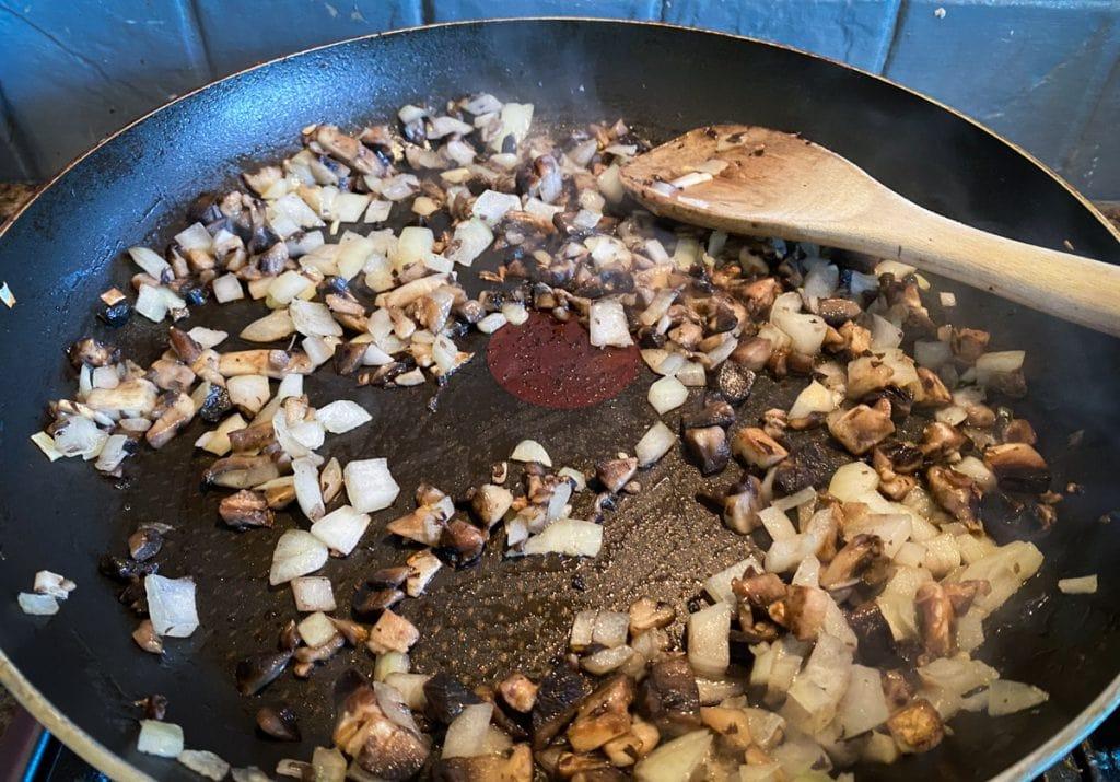 Onion and mushroom frying in a pan for vegan haggis recipe