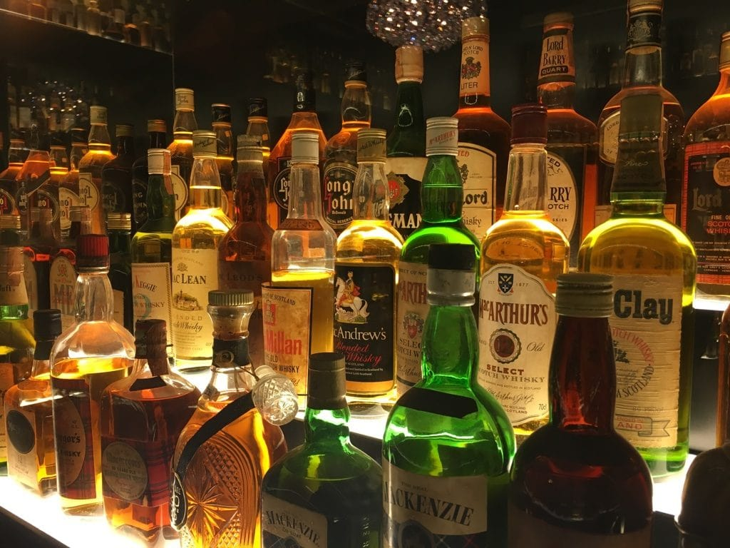 Bottles of Whisky lit behind glass at the Scotch Whisky Experience in Edinburgh