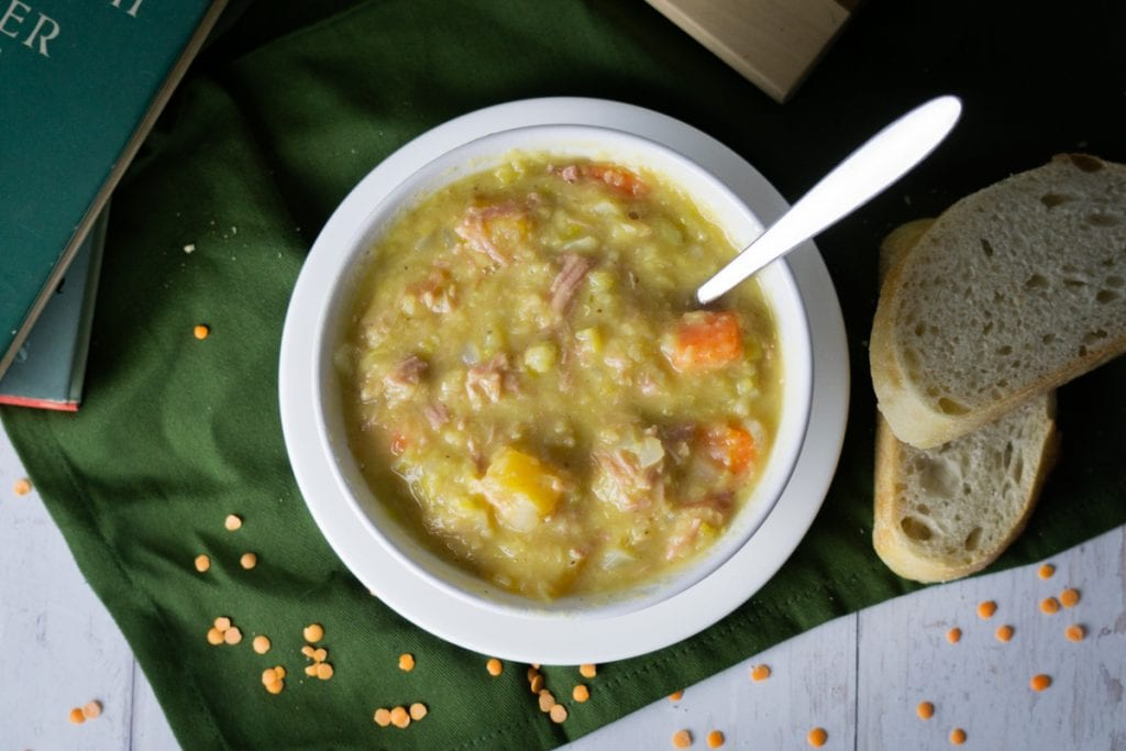 Scottish Lentil and Ham Hock Soup - Lentil and Ham Soup in a bowl with bread and books and lentils scattered about
