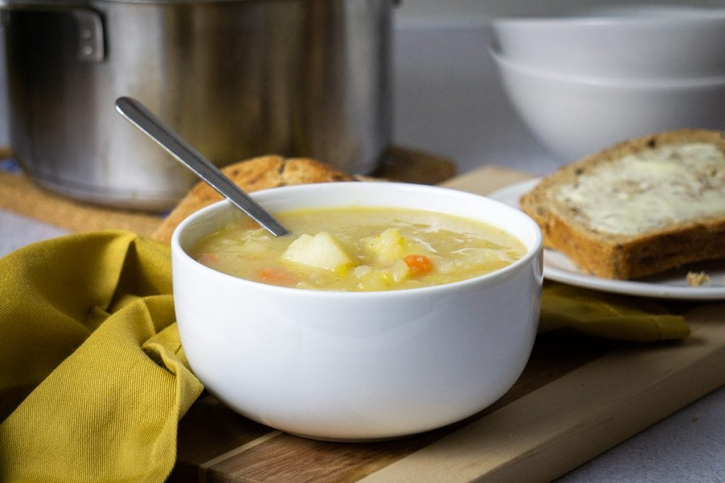 Scottish Potato Soup and Tattie Soup Recipe in a bowl with bread and potatoes beside