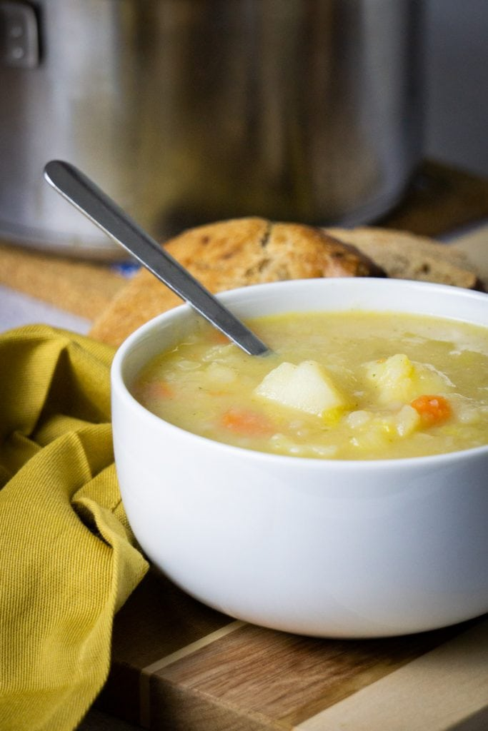 Scottish Potato Soup and Tattie Soup Recipe in a bowl with bread and potatoes beside and soup pot in the background