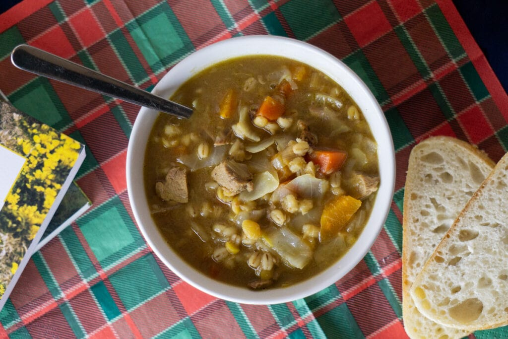 Scotch Broth Recipe in a bowl with bread and books nearby