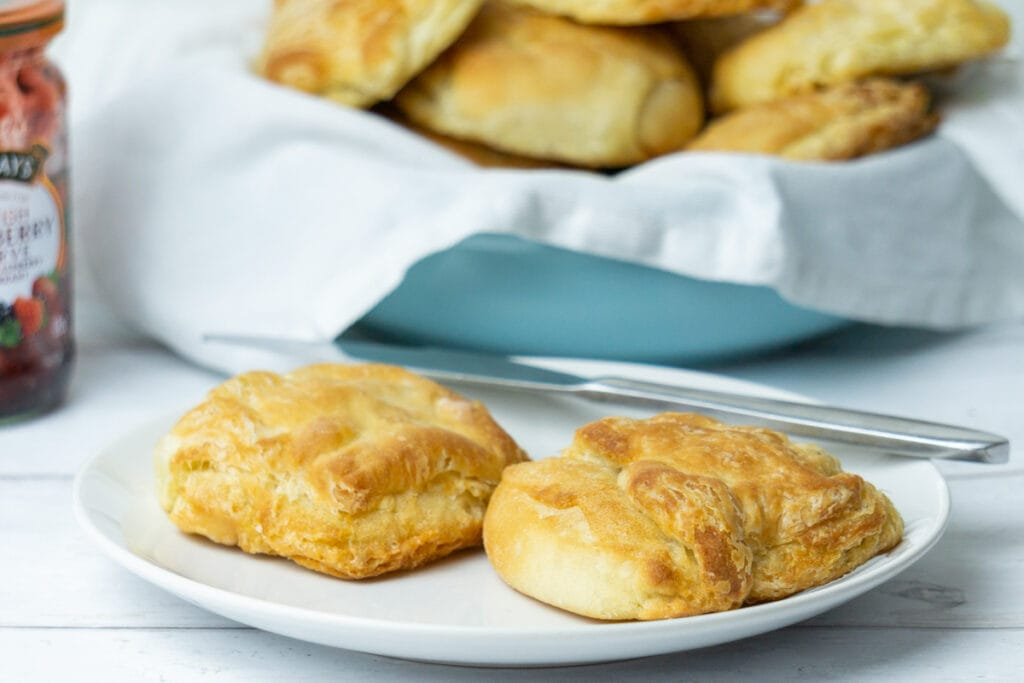 Butteries recipe - Butteries on a plate with jar of jam and bowl of butteries in the background
