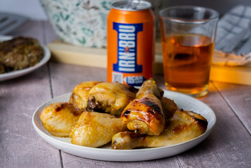 Irn Bru Glaze Recipe on Chicken with can and glass of Irn Bru in the background